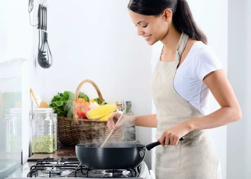 Woman standing by the stove in the kitchen, cooking and smelling