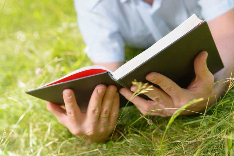 Man reading book outside
