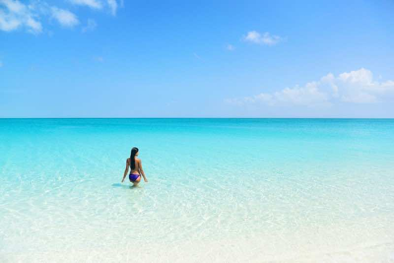 Beach holiday person swimming in blue ocean. Sexy bikini woman r