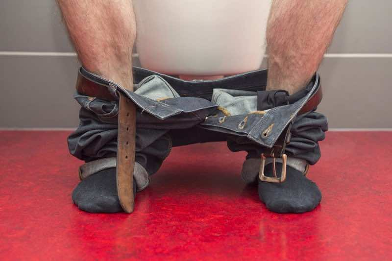 closeup of man with jeans sitting on a toilet