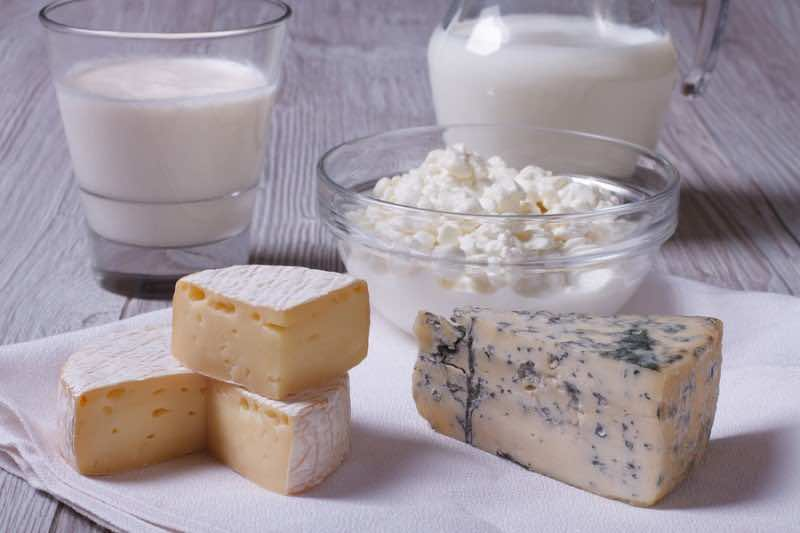 Brie, Blue Cheese, Cottage Cheese And Milk On The Table Closeup
