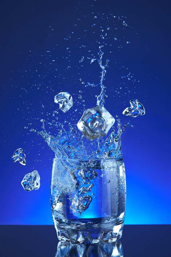 Water splash poured into a glass, blue background, refreshing, f