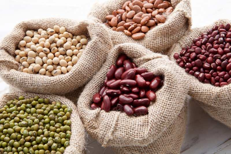 Assortment Of Beans And Lentils In Hemp Sack On Wooden Backgroun