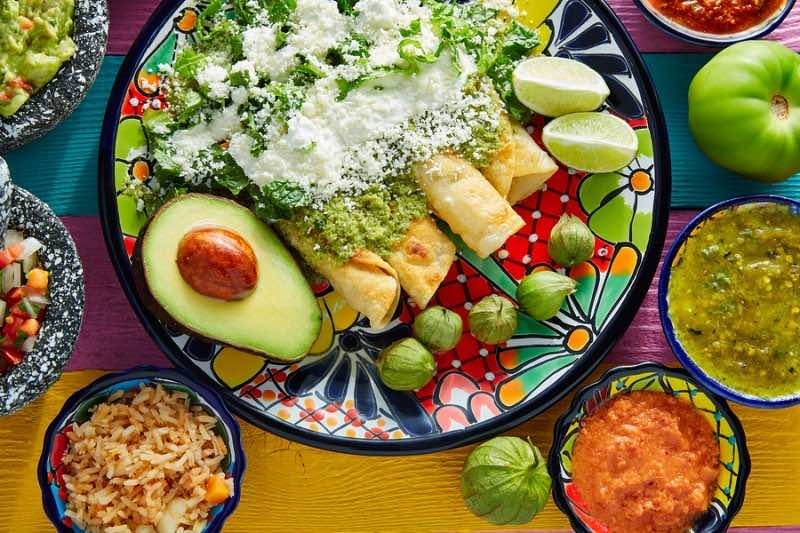 Green enchiladas Mexican food with guacamole and sauces on color