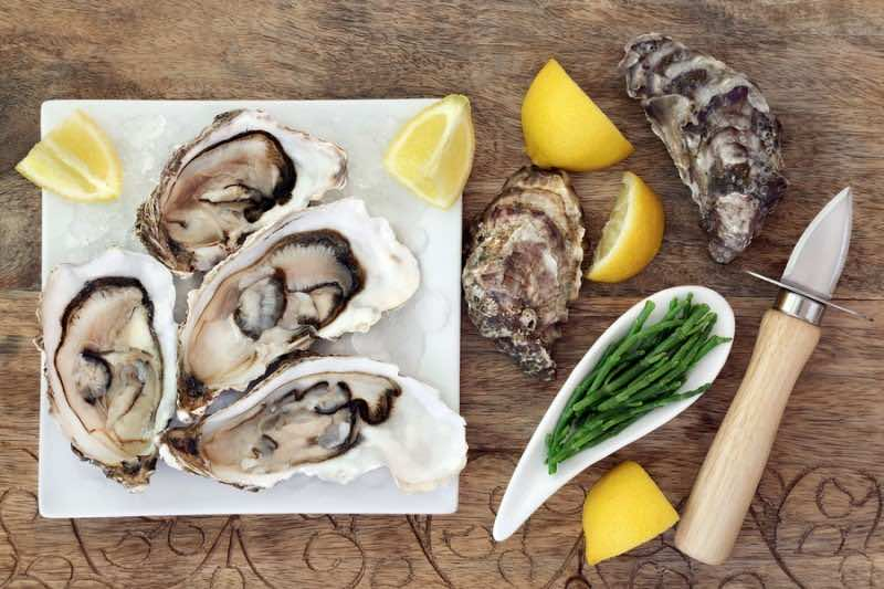 Oysters on crushed ice on a square china plate with oyster knife