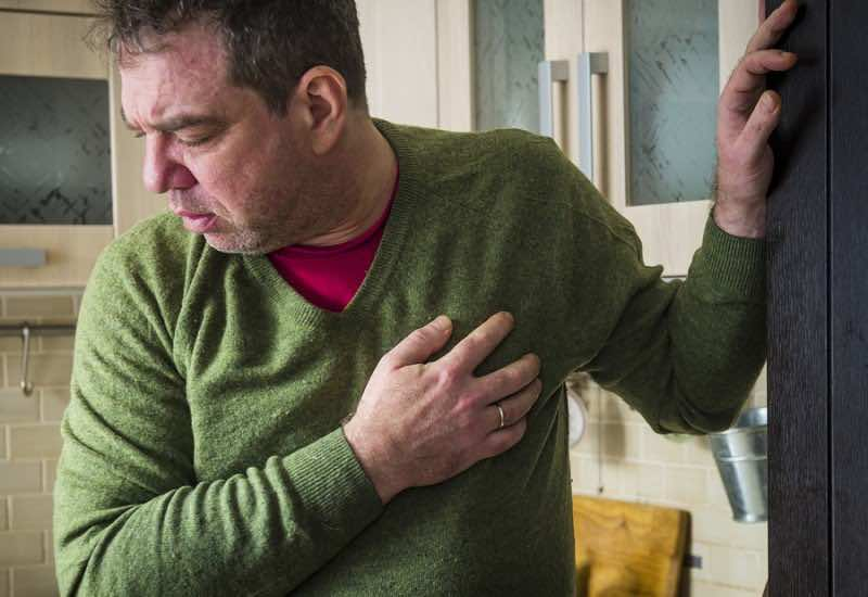 Heart attack. Mature man in home clothes holding her hand to her