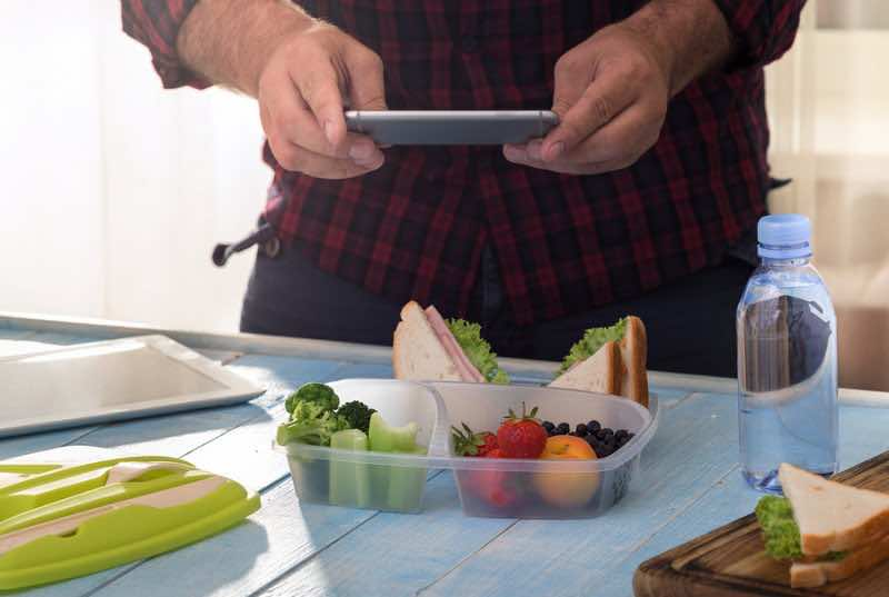 Man photographing lunch box with healthy food.