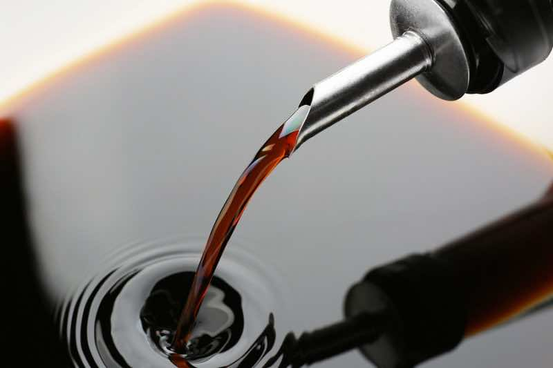 Pouring tasty soy sauce from bottle, closeup