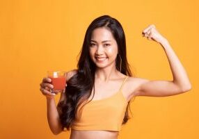 Strong healthy Asian woman with tomato juice on yellow background