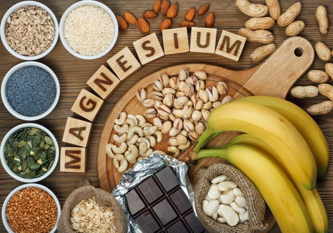 Products containing magnesium: bananas, pumpkin seeds, blue poppy seed, cashew nuts, beans, almonds, sunflower seeds, oatmeal, buckwheat, peanuts, pistachios, dark chocolate and sesame seeds on wooden table