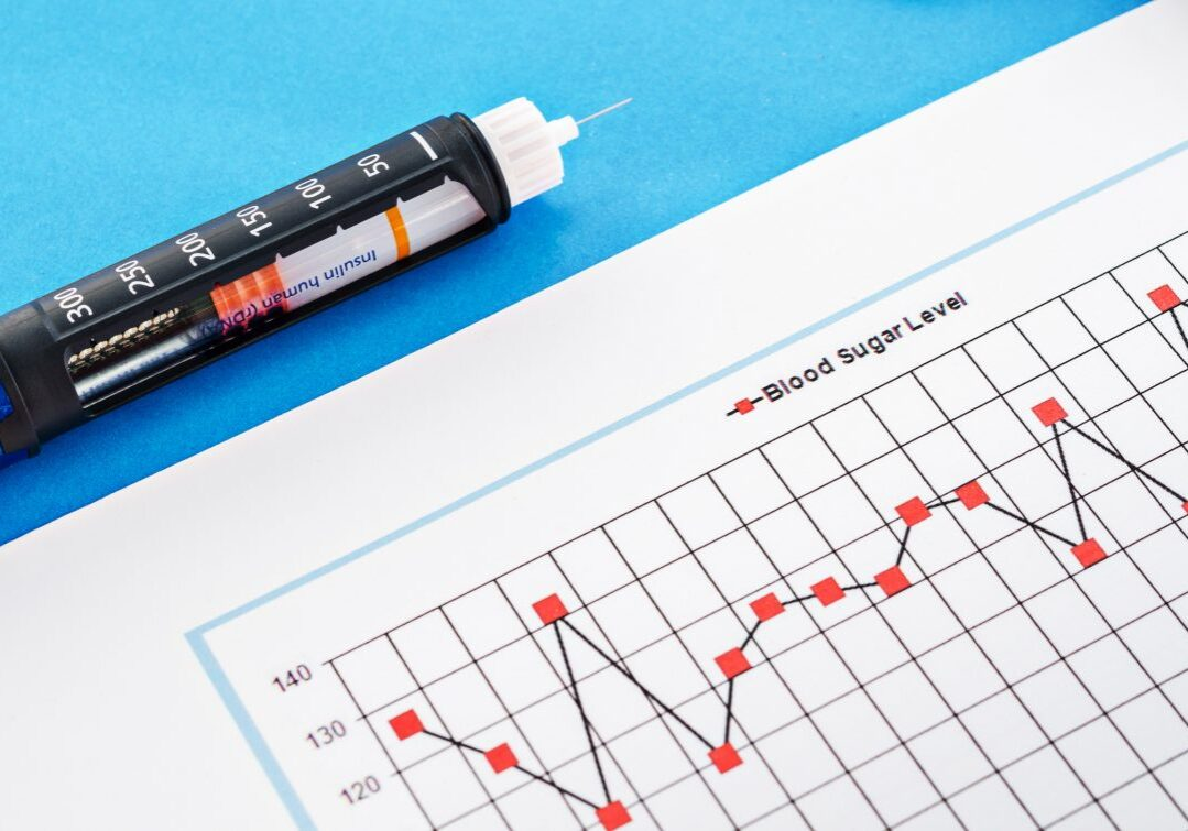 Insulin injection pen with blood sugar level monitoring chart on blue background.