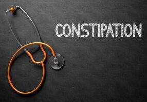 Medical Concept: Constipation on Black Chalkboard. Constipation Handwritten Medical Concept on Chalkboard. Top View Composition with Black Chalkboard and Orange Stethoscope on it. 3D Rendering.