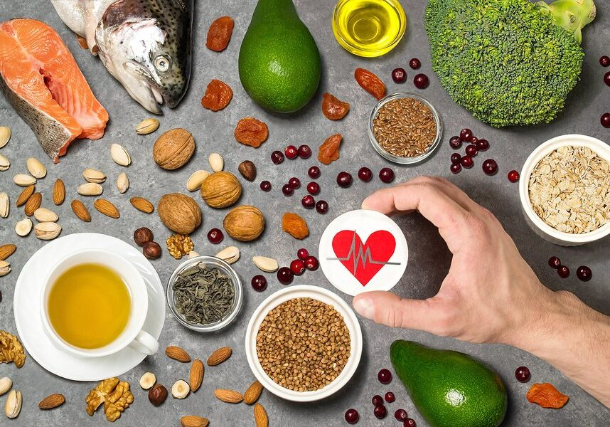 Food products useful for heart. Set of natural food products are sources of vitamins and minerals. Man's hand holds tag with homemade application from paper - symbol of heart. Top view