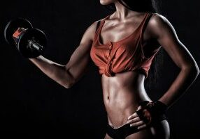 beautiful woman on a dark background is engaged in fitness