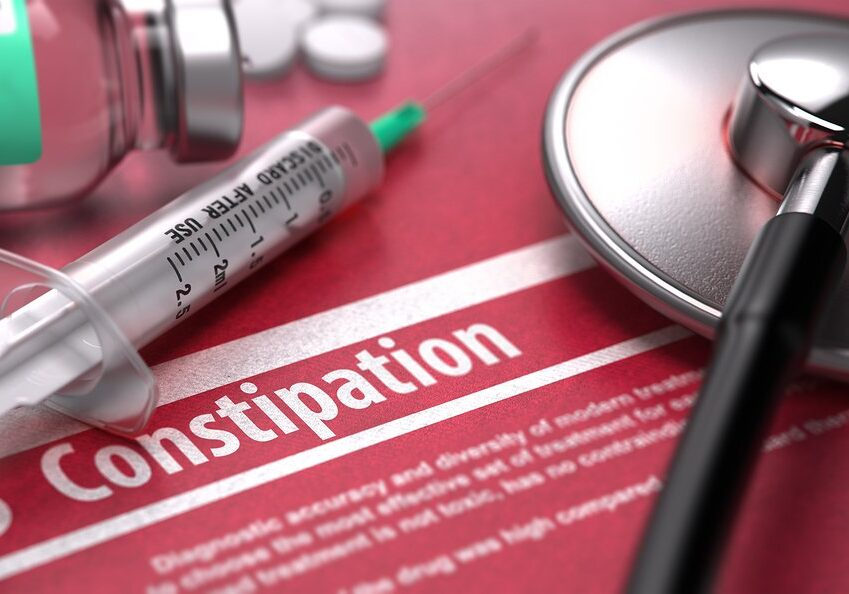 Constipation - Medical Concept on Red Background with Blurred Text and Composition of Pills, Syringe and Stethoscope.