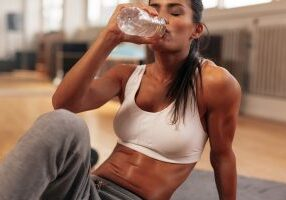 Fitness woman drinking water from bottle. Muscular young female at gym taking a break from workout. ** Note: Shallow depth of field