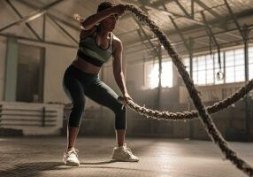 Fitness woman using training ropes for exercise at gym. Athlete working out with battle ropes at  gym.