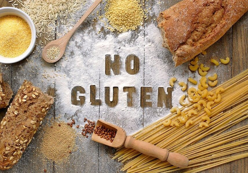 Gluten free flour and cereals millet quinoa corn flour polenta brown buckwheat basmati rice bread and pasta with text no gluten in English language with spoon on brown wooden backgroundup view