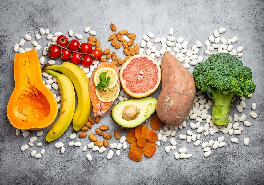 Vegetables, fruit and foods containing potassium over gray stone background, top view. Natural sources of potassium, vitamins and micronutrients for healthy balanced diet and avitaminosis prevention