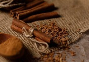 Finely chopped cinnamon and cinnamon sticks on a textured background with textiles. Top view. Space under your text.