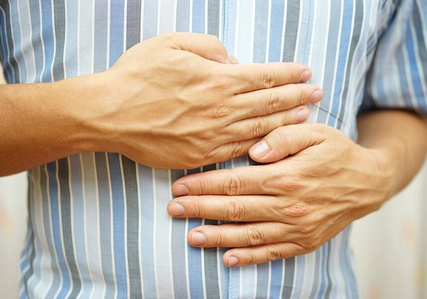 Stomach ache man placing hands on the stomach concept of  stomach ulcer