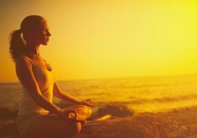 yoga in the beach. woman meditating in lotus pose on the beach at sunset