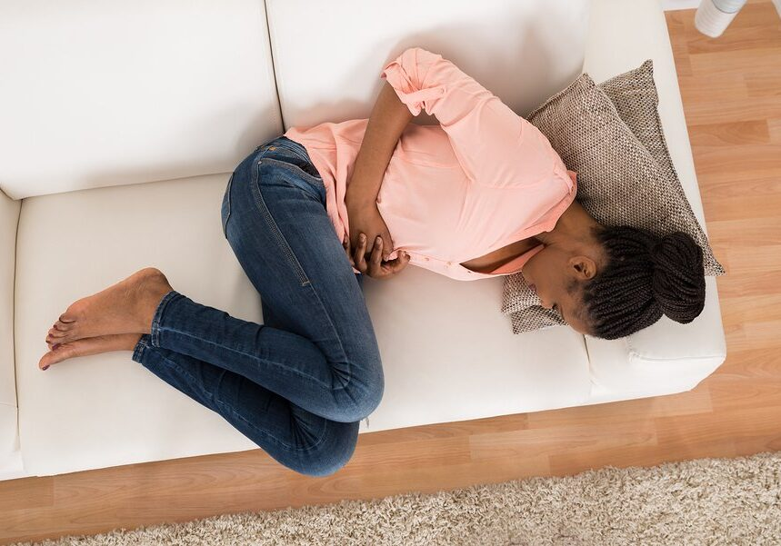 High Angle View Of Young African Woman With Stomach Ache Lying On Sofa