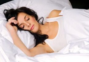 Beautiful brunette young woman sleeping in her bed