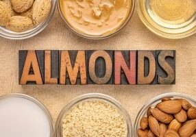 collection of almond super foods: nuts, flour, slices, milk, oils and butter - top view of small glass with almonds word in vintage letterpress wood type