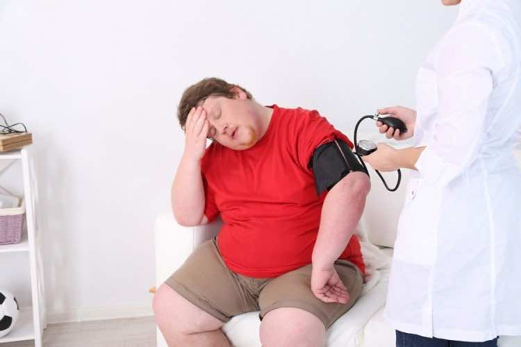 Doctor examining  patient obesity on light background