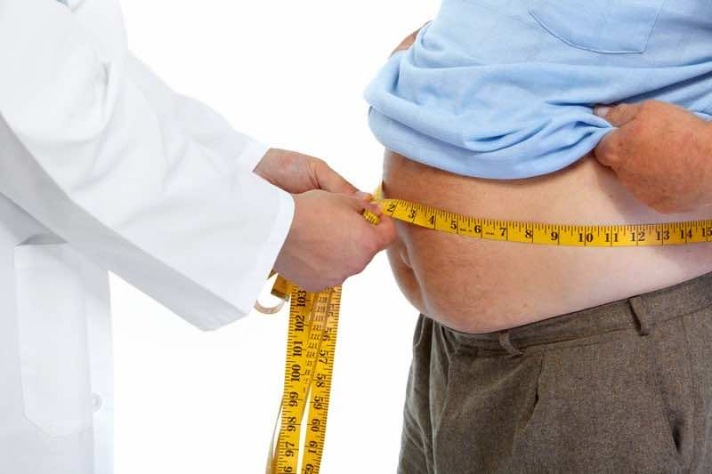 Doctor measuring obese man waist body fat. Obesity and weight lo