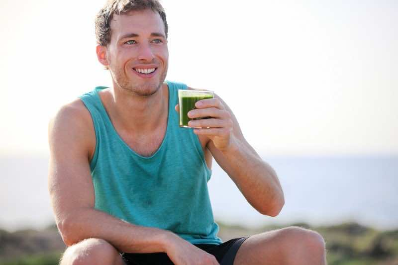 Green smoothie man drinking vegetable juice after running sport