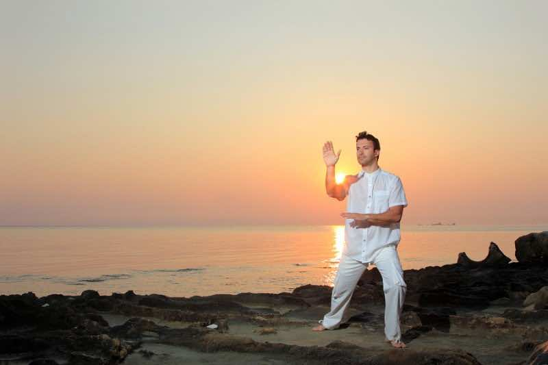 Handsome man practicing thai chi on the beach at sunrise
