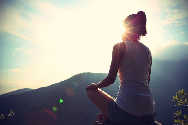 young yoga woman sit meditation on sunrise mountain peak rock