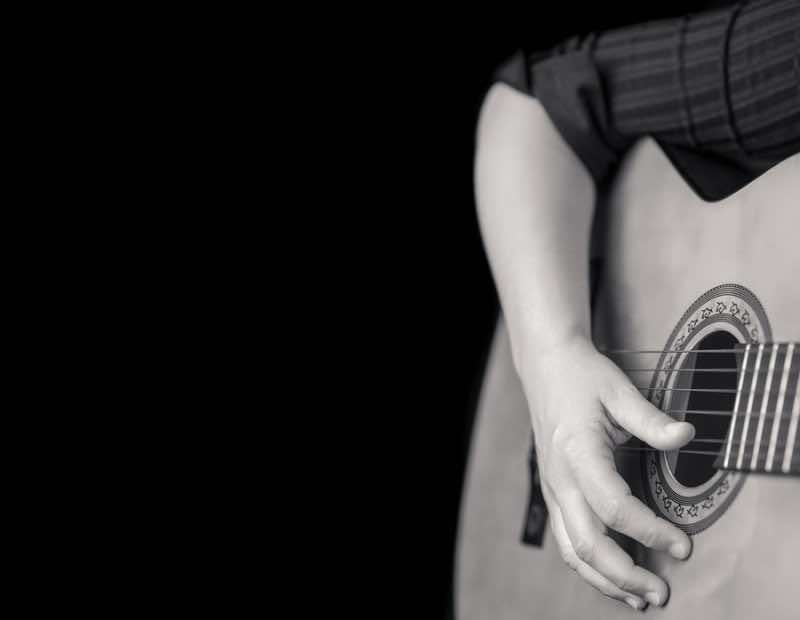 Acoustic guitar detail on black and white - Musician hands playi