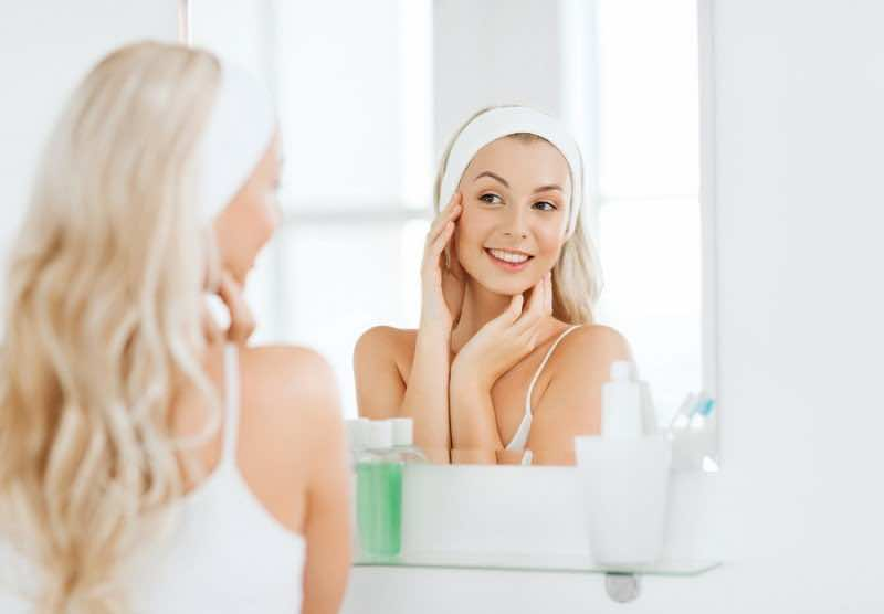 beauty, skin care and people concept - smiling young woman in ha