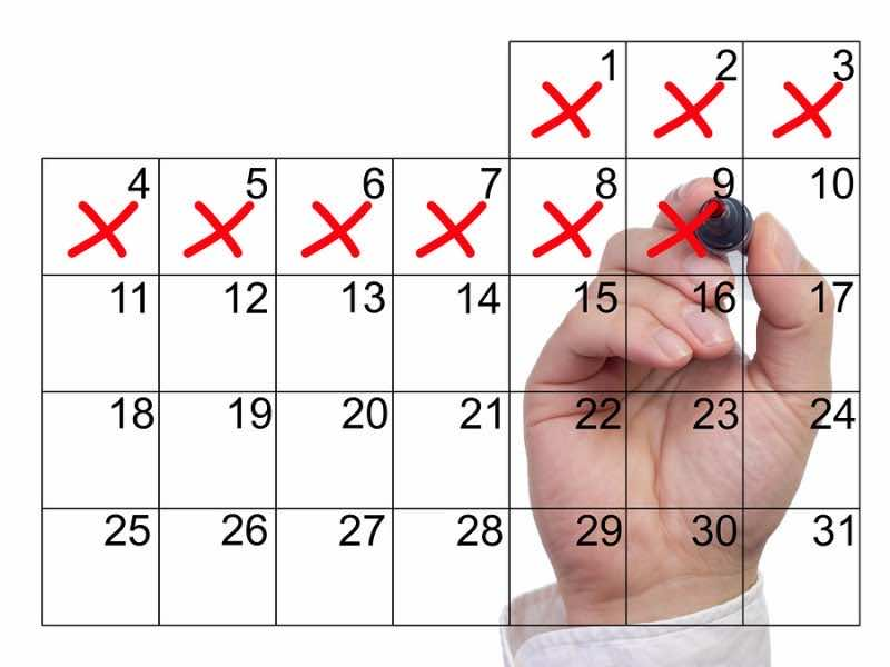 Hand crosses off days in red from a calendar on the screen on white background