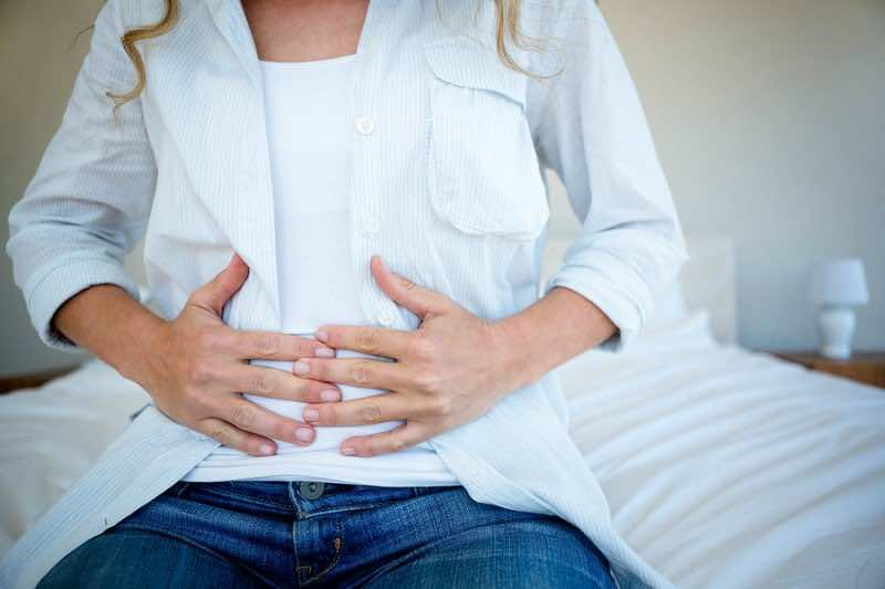 woman sitting on her bed clutching her stomach in discomfort