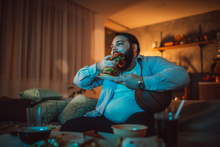One man, sitting at home, eating burgers and watching a sports match alone.